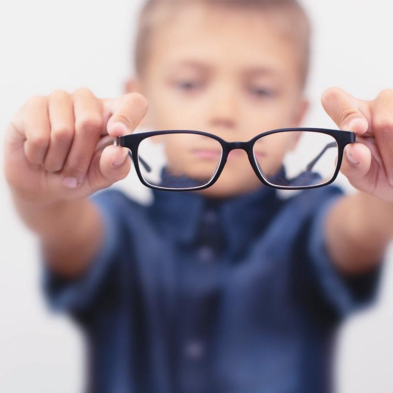 enfant flou tenant une paire de lunettes